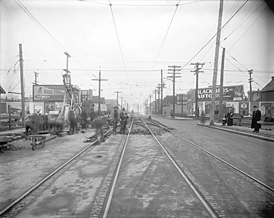 Men excavating street and laying streetcar tracks on Fourth Avenue, looking east from Fir Street